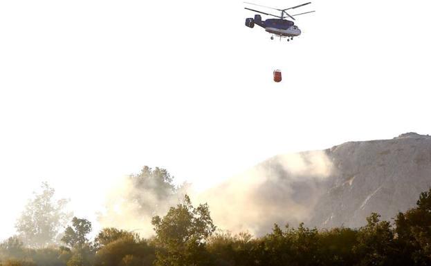 Un helicóptero trata de socorrer las llamas.