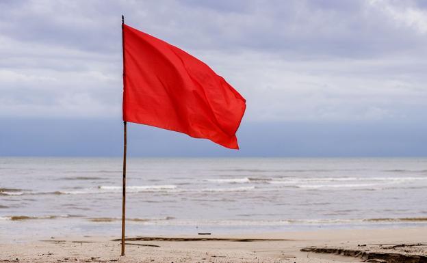 Imagen de una bandera roja en una playa.