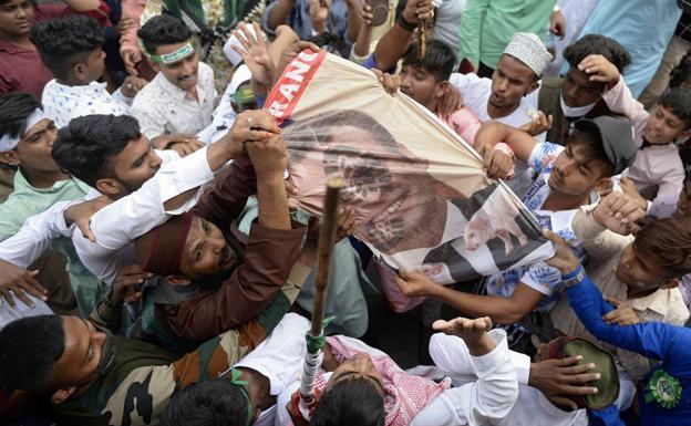 Un grupo de musulmanes destruye un cartel con el rostro de Macron en un pueblo de India.